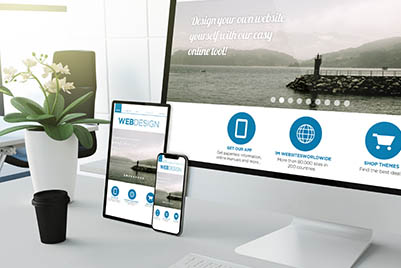 desktop, ipad and iphone on a desk showing web design on the screens